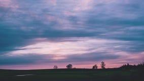 Ένα θαυμάσιο ηλιοβασίλεμα πέρα από έναν τομέα με τα ρόδινα χρώματα στα σύννεφα απόθεμα βίντεο