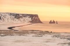 Ένα θερμό ηλιοβασίλεμα πέρα από μια χιονώδη ακτή στην Ισλανδία Στοκ Φωτογραφία