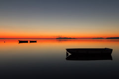 Ένα θερμό ηλιοβασίλεμα σε ένα ήρεμο νερό, με τα νησιά στο υπόβαθρο Στοκ φωτογραφίες με δικαίωμα ελεύθερης χρήσης