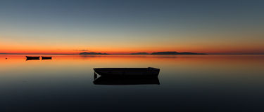 Ένα θερμό ηλιοβασίλεμα σε ένα ήρεμο νερό, με τα νησιά στο υπόβαθρο Στοκ φωτογραφία με δικαίωμα ελεύθερης χρήσης
