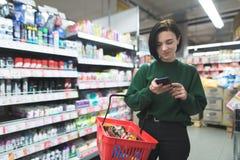 Ένα θετικό κορίτσι χρησιμοποιεί ένα τηλέφωνο σε μια υπεραγορά Ένα κορίτσι που ψωνίζει σε μια υπεραγορά με ένα τηλέφωνο στα χέρια  Στοκ φωτογραφία με δικαίωμα ελεύθερης χρήσης