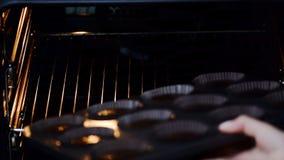 Ένα θηλυκό χέρι βάζει έναν δίσκο ψησίματος με τη χειροποίητη muffin ` s ζύμη μέσα σε έναν εγχώριο φούρνο φιλμ μικρού μήκους