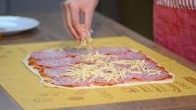 Ένα θηλυκό χέρι ψεκάζει μια πίτσα με την ξυμένη κινηματογράφηση σε πρώτο πλάνο τυριών απόθεμα βίντεο