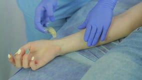 Ένα θηλυκό cosmetician εφαρμόζει την κόλλα ζάχαρης στο δέρμα των χεριών πελατών ` s φιλμ μικρού μήκους