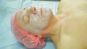 Ένα θηλυκό cosmetologist που φορά τα γάντια εφαρμόζει μια μάσκα φυκιών σε ένα πρόσωπο ατόμων s με μια βούρτσα απόθεμα βίντεο