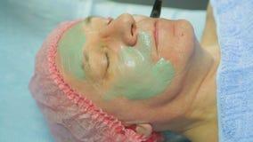 Ένα θηλυκό cosmetologist στα γάντια εφαρμόζει μια θεραπευτική μάσκα αργίλου σε ένα πρόσωπο ατόμων s με μια βούρτσα απόθεμα βίντεο