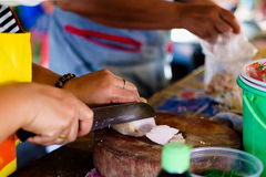 Ένα θηλυκό τεμαχίζοντας χοιρινό κρέας πλανόδιων πωλητών για το μαγείρεμα Στοκ Φωτογραφία