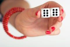 Ένα θηλυκό χέρι που κρατά δύο χωρίζει σε τετράγωνα και που παρουσιάζει διπλάσιο έξι Στοκ Φωτογραφίες
