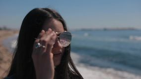 Ένα θολωμένο πορτρέτο ενός κοριτσιού ενάντια στη φυσική άποψη της παραλίας και της θάλασσας τη σαφή ηλιόλουστη ημέρα Το κορίτσι β φιλμ μικρού μήκους