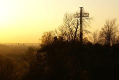 Ένα διαγώνιο μνημείο που αγνοεί ένα misty τοπίο πόλεων στο ηλιοβασίλεμα Στοκ Εικόνα