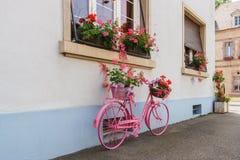 Ένα διακοσμητικό παλαιό ρόδινο ποδήλατο με ένα καλάθι λουλουδιών κοντά σε ένα buildi Στοκ Φωτογραφία