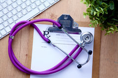 Ένα ιατρικό στηθοσκόπιο κοντά σε ένα lap-top σε έναν ξύλινο Στοκ φωτογραφία με δικαίωμα ελεύθερης χρήσης