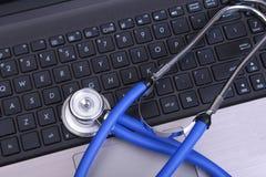 Ένα ιατρικό στηθοσκόπιο κοντά σε ένα lap-top σε έναν ξύλινο πίνακα Στοκ Εικόνες