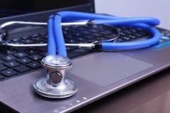 Ένα ιατρικό στηθοσκόπιο κοντά σε ένα lap-top σε έναν ξύλινο πίνακα Στοκ εικόνες με δικαίωμα ελεύθερης χρήσης