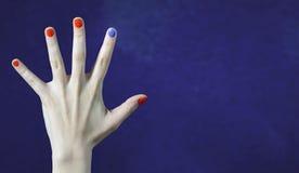 Ένα διαφορετικό χρώμα καρφιών στο δάχτυλο στο καυκάσιο χέρι Κόκκινα και μπλε χρωματισμένα νύχια στοκ φωτογραφίες με δικαίωμα ελεύθερης χρήσης