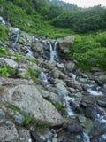 Ένα ισχυρό ρεύμα βουνών ρέει κάτω από τους βράχους και τις πέτρες στοκ φωτογραφία
