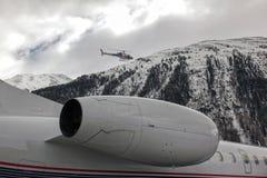 Ένα ιδιωτικό αεριωθούμενο αεροπλάνο και ένα πετώντας ελικόπτερο στον αερολιμένα του ST Moritz Στοκ Εικόνες