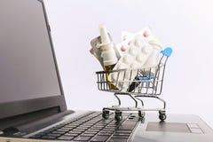 Ένα κάρρο αγορών με τα φάρμακα και τα χάπια είναι στο lap-top E στοκ φωτογραφίες