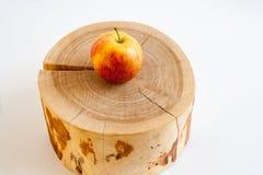 Ένα κίτρινος-κόκκινο μήλο βρίσκεται στο ξύλινο κολόβωμα στο άσπρο backgroun Στοκ Εικόνα