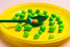 Ένα κίτρινο πλαστικό πιάτο που γεμίζουν με την καραμέλα με ένα πράσινο κουτάλι σε ένα ρόδινο υπόβαθρο στοκ εικόνα με δικαίωμα ελεύθερης χρήσης