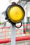 Ένα κίτρινο φως σημάτων με την κόκκινη πύλη εμποδίων Στοκ Εικόνες