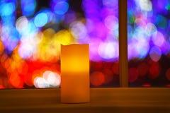 Ένα καίγοντας κερί στο παράθυρο στα πλαίσια των ακτινοβολώντας ζωηρόχρωμων φω'των στοκ φωτογραφίες