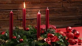 Ένα καίγοντας κόκκινο κερί σε ένα παραδοσιακό στεφάνι εμφάνισης με την εορταστική διακόσμηση απόθεμα βίντεο