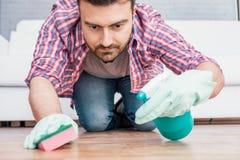 Ένα καθαρίζοντας πάτωμα παρκέ ατόμων με το σφουγγάρι στοκ φωτογραφίες με δικαίωμα ελεύθερης χρήσης
