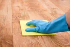 Ένα καθαρίζοντας πάτωμα παρκέ χεριών στοκ εικόνες