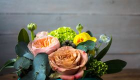 Ένα καλάθι των όμορφων λουλουδιών σε ένα ξύλινο υπόβαθρο στοκ εικόνα με δικαίωμα ελεύθερης χρήσης