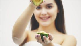 Ένα καλό νέο κορίτσι που στέκεται σε ένα άσπρο υπόβαθρο Μια υγιής ελκυστική γυναίκα brunette κρατά στα χέρια της ένα αβοκάντο απόθεμα βίντεο