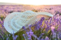 Ένα καπέλο αχύρου βρίσκεται σε έναν lavender τομέα, εκλεκτική εστίαση Dawn στο lavender τομέα Η έννοια του ταξιδιού, ομορφιά o στοκ φωτογραφία