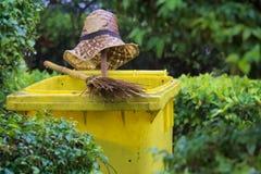Ένα καπέλο αχύρου, μια απλή ταϊλανδική σκούπα και ένα κίτρινο δοχείο απορριμάτων  όλοι που εγκαταλείπονται γρήγορα λόγω μιας ξαφν Στοκ εικόνες με δικαίωμα ελεύθερης χρήσης