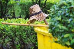 Ένα καπέλο αχύρου, μια απλή ταϊλανδική σκούπα και ένα κίτρινο δοχείο απορριμάτων  όλοι που εγκαταλείπονται γρήγορα λόγω μιας ξαφν Στοκ Εικόνες
