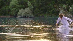 Ένα καταβρέχοντας νερό ζευγών αγάπης σε μια λίμνη το καλοκαίρι απόθεμα βίντεο