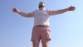 Ένα καυκάσιο άτομο με μια γενειάδα συμμετέχει στη δυναμική γιόγκα στις όχθεις του ποταμού, μια αμμώδης παραλία, μια επέκταση δικο απόθεμα βίντεο