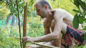 Ένα καυκάσιο άτομο που χρησιμοποιεί το ξύλο μπαμπού για την οικοδόμηση του φυσικού φράκτη στον κήπο απόθεμα βίντεο