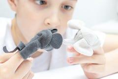 Ένα καυκάσιο αγόρι που διαδραματίζει τους διαφορετικούς ρόλους με τη χρησιμοποίηση των μαριονετών δάχτυλων, των παιχνιδιών για τη στοκ φωτογραφία με δικαίωμα ελεύθερης χρήσης