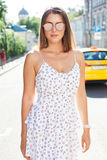 Ένα καυτό καλοκαίρι στην πόλη Πορτρέτο ενός κοριτσιού σε ένα ελαφρύ άσπρο φόρεμα και τα γυαλιά ηλίου που θέτουν σε ένα καυτό απόγ Στοκ φωτογραφίες με δικαίωμα ελεύθερης χρήσης