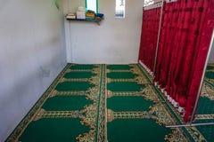 Ένα κενό μουσουλμανικό τέμενος με τον πράσινο τάπητα και κόκκινη κουρτίνα ως εμπόδιο μεταξύ του διαστήματος ανδρών και γυναικών Στοκ φωτογραφία με δικαίωμα ελεύθερης χρήσης