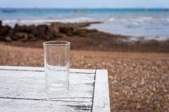 Ένα κενό ποτήρι του νερού είναι στον άσπρο ξύλινο πίνακα στην παραλία Στοκ Φωτογραφία