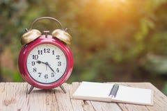 Ένα κενό σημειωματάριο στηρίζεται σε ένα ξύλινο μπαλκόνι Με ένα ρολόι στοκ φωτογραφία με δικαίωμα ελεύθερης χρήσης