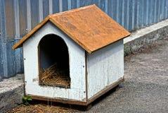Ένα κενό σκυλόσπιτο του κοντραπλακέ κοντά σε έναν φράκτη σιδήρου Στοκ Εικόνες