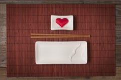 Ένα κεραμικό πιάτο για τα σούσια και τα ιαπωνικά τρόφιμα με chopstick και κύπελλο για τη σάλτσα σόγιας με μια καρδιά μέσα στη τοπ στοκ φωτογραφία
