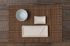 Ένα κεραμικό πιάτο για τα σούσια και τα ιαπωνικά τρόφιμα με chopstick και κύπελλο για τη σάλτσα σόγιας στη τοπ άποψη χαλιών μπαμπ στοκ εικόνα με δικαίωμα ελεύθερης χρήσης