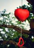 Ένα κινητό πήλινο είδος και 2 κόκκινες καρδιές που κρεμούν στο befo δέντρων στοκ φωτογραφία με δικαίωμα ελεύθερης χρήσης