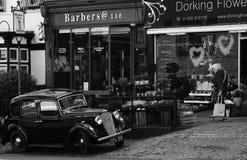 Ένα κλασικό ροδοκόκκινο αυτοκίνητο του Ώστιν στάθμευσε τα εξωτερικά σύγχρονα καταστήματα Στοκ Φωτογραφία