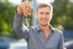 Ένα κλειδί χεριών ατόμων ` s από το αυτοκίνητο με τα κουμπιά σε ανοικτό ή κλείνει την κλειδαριά πορτών αυτοκινήτων Τυχερός ιδιοκτ στοκ εικόνες