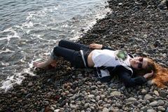 Ένα κοκκινομάλλες κορίτσι βρίσκεται σε μια παραλία χαλικιών και τα πόδια της χαμηλώνουν στα κύματα στοκ εικόνα με δικαίωμα ελεύθερης χρήσης