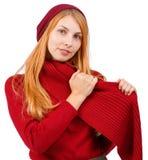 Ένα κοκκινομάλλες κορίτσι είναι ντυμένο στο κόκκινο είναι τυλιγμένο γύρω από το λαιμό της με ένα κόκκινο μαντίλι η ανασκόπηση απο στοκ φωτογραφίες